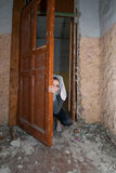 Girl behind door Stock Image