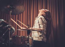 Girl behind drums on a rehearsal. Young cheerful girl behind drums on a rehearsal royalty free stock images