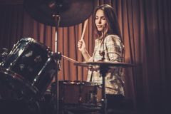 Girl behind drums on a rehearsal. Young cheerful girl behind drums on a rehearsal stock images