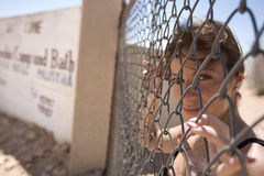 Girl behind a fence. Girl with brown eyes is standing behind a fence Royalty Free Stock Photo