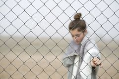 Girl behind a fence. Royalty Free Stock Images