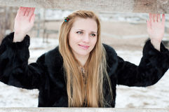 Girl behind the fence. Young blonde woman standing behind a fence in the winter when there is snow Stock Photography