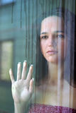 The girl behind glass Stock Photography