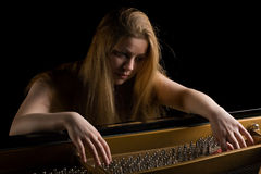 Girl behind a grand piano Stock Images