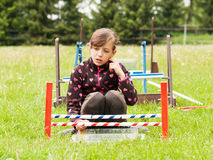 Girl behind hurdle for rabbit Royalty Free Stock Photography