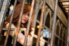 Girl behind metal bar Stock Photos