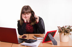 Girl behind office desk listening to cry of the phone Royalty Free Stock Photo