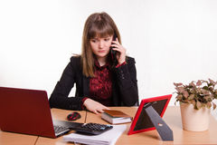 Girl behind office desk on phone listening to a friend Royalty Free Stock Photography