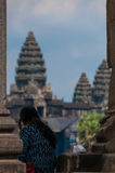 Girl from behind sitting in front of Angkor Wat Stock Images