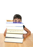 Girl behind stack of books. Cute young girl looking over high stack of books, isolated on white background Royalty Free Stock Photography