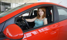 The girl behind the steering wheel of a car. Young woman looking out the side window while driving a red car Royalty Free Stock Image