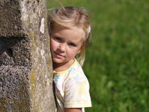 Girl behind the Stone Bollard Royalty Free Stock Photo