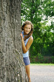 Girl behind a tree Royalty Free Stock Image