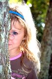 Girl behind a tree. Young girl, looking out from behind a tree, with a sweet smile royalty free stock photography