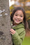 Girl behind the tree royalty free stock image