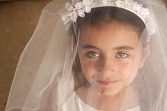 Girl behind veil. A young girl in her holy communion outfit looking at the camera from behind her veil. Stunning green eyes Royalty Free Stock Photos
