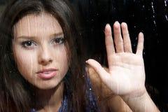 Girl behind wet window Royalty Free Stock Image