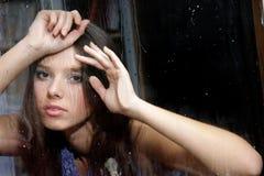 Girl behind wet window Stock Images