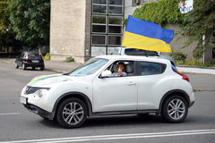 The girl behind the wheel of a car, to which a Ukrainian flag Stock Image