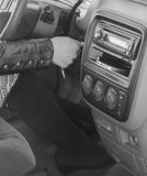 The girl behind the wheel of a car turns the ignition key, black. Black and white, in the driver`s seat of the car, the girl starts the engine Royalty Free Stock Images
