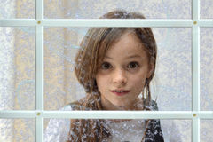 Girl behind the window. Cute teenager girl behind a window with frozen patters Royalty Free Stock Photography
