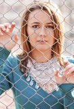 Girl behind a wire fence Royalty Free Stock Image