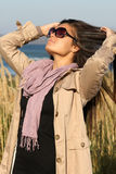 Girl in beige autumn coat correcting her hair Royalty Free Stock Image