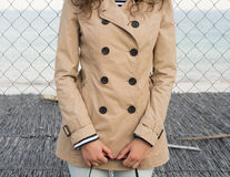 Girl in a beige coat on the coast. Slender girl in a beige coat with buttons on the coast. In the background you can see the sea Stock Image