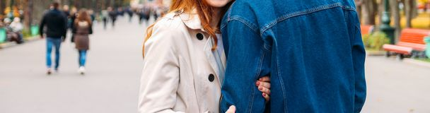 Girl in a beige coat holding the hand of a guy in a denim jacket who is trying to leave, parting, leaving, breaking up. stock photo