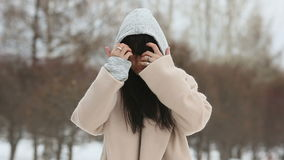 Girl in beige coat straightens, hands combing hair. Young beautiful stylish girl with long dark hair walking outdoors in gray coat in park. Closeup portrait stock footage