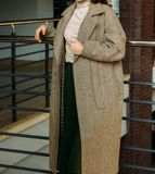 A girl in a beige coat and sweater, a green, long skirt, stands near the railing, leaning on a metal railing. rest, fashion show, stock photos