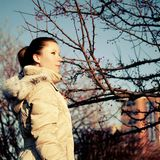 Girl in beige dawn parka, red berry tree Stock Photos