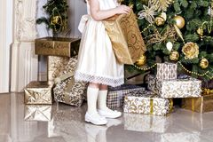 A girl in beige dress decorating Christmas tree with glass Christmas balls and toys. Stock Photography