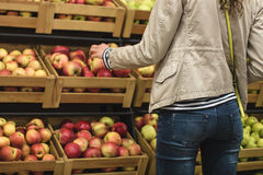 Girl in the beige jacket and blue jeans buys apples. Girl in the beige jacket and blue jeans picks apples in the supermarket. Girl seen from the back. In the Royalty Free Stock Photo