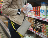 Girl in the beige jacket and blue jeans buys dairy products Royalty Free Stock Image