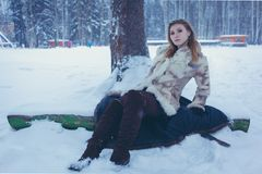 Girl in a beige short fur coat and brown boots with flowing hair is sitting on the snow near the tree stock image