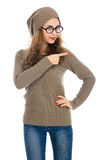 Girl in a beige sweater showing thumb to the side. Warning, adve Royalty Free Stock Image