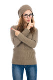 Girl in a beige sweater showing thumb to the side. Warning, adve Royalty Free Stock Photos