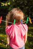 Girl being hanged by shirt on clothesline Royalty Free Stock Photography