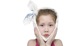 Girl being ill. 8-year-old girl with a bandage around her face as if she has got a toothache royalty free stock images
