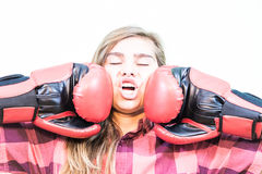 Girl being punched. Teenage girl is being punched with two boxing gloves. White background Royalty Free Stock Photo