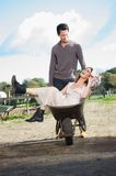 Girl Being Pushed in Wheelbarrow by Man Stock Photography