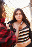 Girl Being Threatened With Knife By Female Gang Member. By Fence Looking Worried royalty free stock images