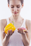 Girl with bell pepper and donut Royalty Free Stock Images