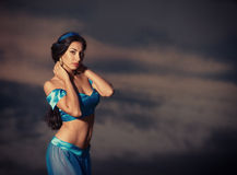 Girl in belly dance costume at sunset