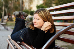 Girl on a bench. Young women lies on a bench in a park Stock Photos