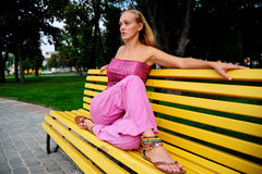 Girl on a bench. Girl sitting on a park bench arms outstretched Royalty Free Stock Photos
