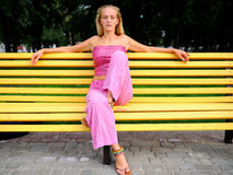 Girl on a bench. Girl sitting on a park bench arms outstretched Royalty Free Stock Images