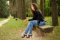 Girl on a bench. In a park avenue Stock Photography