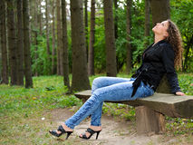 Girl on a bench. In a park avenue Royalty Free Stock Photo